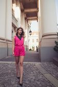 picture of jumpsuits  - Fashion glamorous and attractive woman dressed in a sexy sleeveless pink jumpsuit walking on imaginary catwalk on street - JPG