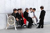 Ashgabat, Turkmenistan - May 25. Group Of Asian Children Sitting On A Bench And Talking.  Ashgabat,