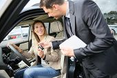 Car dealer giving key to new car owner