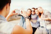 summer holidays and technology concept - close up of female hands holding digital camera and making