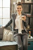 Smiling Business Woman With Coffee Latte Sitting On Divan In Lof