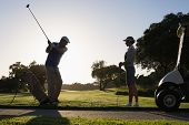 stock photo of take off clothes  - Golfing couple teeing off for the day on a sunny morning at the golf course - JPG