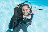 Smiling woman on scuba training in swimming pool making ok sign on a sunny day