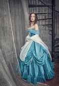 Beautiful Woman In Blue Medieval Dress On The Stairway