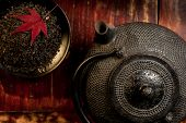 stock photo of teapot  - Japanese iron teapot and heap of tea leaves from top - JPG