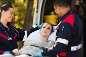 stock photo of stretcher  - friendly paramedics talking to patient on stretcher - JPG