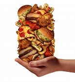 stock photo of junk  - Over eating and compulsive indulgence of fast food concept as a hand holding up a huge stack of junk food as hamburgers hotdogs and french fries as an unhealthy diet nd bad nutrition symbol isolated on a white background - JPG