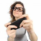 stock photo of crazy face  - Geek woman playing with a smart phone isolated on a white background - JPG