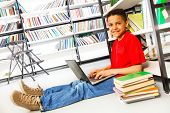 Smiling boy with books and laptop in library