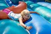 stock photo of inflatable slide  - Small blonde girl lying on a inflatable blow - JPG