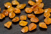 foto of uncut  - Set of uncut rough and raw yellow sapphire gemstones on black stone plate - JPG