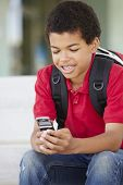 pic of pre-teen boy  - Pre teen boy with phone at school - JPG