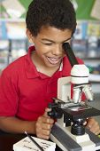 pic of pre-teen boy  - Boy in science class with microscope - JPG