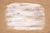 Beach sand on wooden background with plenty of copy space