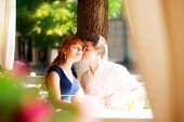 Outdoor Portrait Of Young Sensual Couple In Summer Cafe. Love And Kiss.