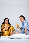 Couple Sit On Bed Drinking Orange Juice