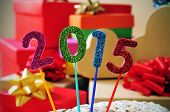 numbers of different colors forming the number 2015, as the new year, with a pile of gifts in the background