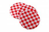 Closeup of Metal preserve jar lids in traditional Gingham pattern, isolated on white