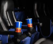 Disposable cold drink glasses in armrests of seats at cinema theater