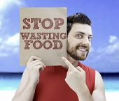 Man holding a card with the text Stop Wasting Food on a beach background