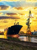 stock photo of shipbuilding  - Cargo ship and the port at sunset - JPG