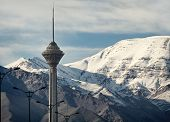 stock photo of tehran  - Milad Tower of Tehran in front of snow covered Alborz Mountains edited with vintage filter - JPG