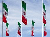 Waving Iranian Flags Against Cloudy Blue Sky