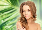 beauty, people and health concept - beautiful young woman with bare shoulders over green palm leaves background