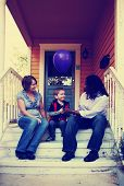 a cute family sitting on a porch toned with a retro vintage instagram filter