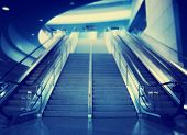 image of escalator  - stairs and an escalator at an airport toned with a retro vintage instagram filter effect - JPG