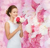 people, wedding, holidays and celebration concept - smiling bride or bridesmaid in white dress with bouquet of flowers over pink floral background