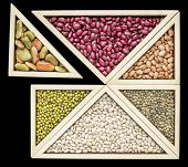 variety of beans and  lentils in a wooden tray inspired by Chinese tangram puzzle, isolated on black