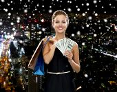 shopping, sale, gifts, money and holidays concept - smiling woman in dress with shopping bags and money over snowy night city background