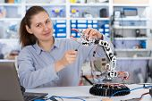 stock photo of robot  - schoolgirl adjusts the robot arm model - JPG