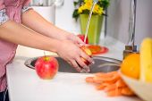 female hands washing apple in the sink home kitchen