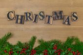 The word Christmas in wooden letters on a rustic background over a fresh green garland with holly and berries.