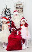 Saint Nicolas embraces two girls near a New Year tree