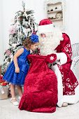 picture of saint-nicolas  - Curious little girl looks in a bag on Saint Nicolas - JPG