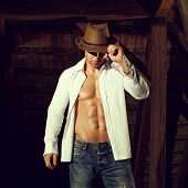 Sexy Man In Hat And Shirt Posing In Barn