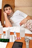 picture of home remedy  - Sad and Sick Teenager on the Sofa at the Home with Pills on foreground - JPG