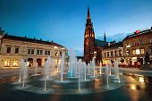 OSIJEK, CROATIA - JUNE 6, 2012: Main city square with fountain and tall cathedral at dusk.