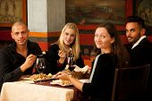Young People Eat Sea Food Dinner At Restaurant And Drink Wine