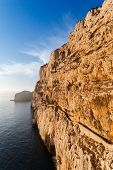 stock photo of grotto  - high cliffs and sea staircase to Neptune Grotto in Sardinia Italy - JPG