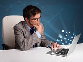 Attractive young man sitting at dest and typing on laptop with message icons comming out