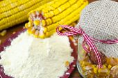 picture of corn  - A jar with corn flour and corn ear on a wooden table - JPG
