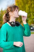 pic of girl walking away  - Happy young student woman drinking take away coffee and walking in an urban city park - JPG