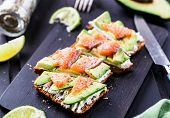stock photo of avocado  - Sandwich with avocado and smoked salmon on a black wooden board - JPG
