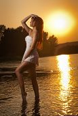 image of tan lines  - Sexy brunette woman in wet white lingerie posing in river water with sunset on background - JPG