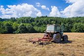 picture of grassland  - Tractor with rotary rakes parked on dry grassland in Cazavet France - JPG