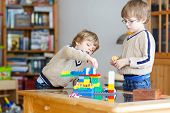 Two Little Kid Friends Playing With Lots Of Colorful Plastic Blocks poster